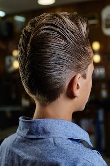 Corte de cabelo de hipster de homens modernos, penteado perfeito para homens com cabelos longos. corte de cabelo retrô no salão de cabeleireiro