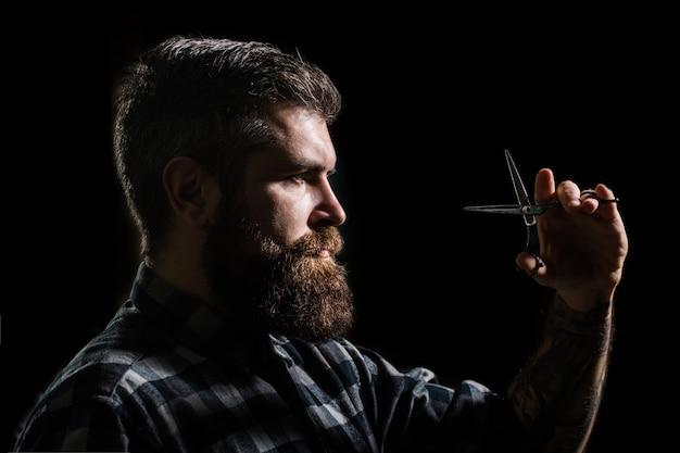 Corte de cabelo do homem na barbearia. perfil de homem elegante barba, tesoura.