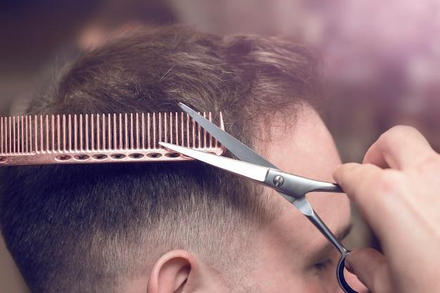 Corte de cabelo estiloso com tesoura em uma barbearia, foco suave