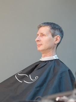 Corte de cabelo masculino em um salão de beleza. homem na cadeira de barbeiro, cabeleireiro cortar o cabelo dele. barbearia.