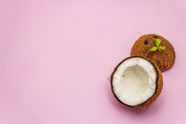 Corte de coco maduro em dois metade isolado em fundo rosa