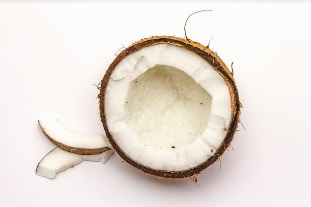 Corte de coco maduro em dois metade isolado no fundo branco