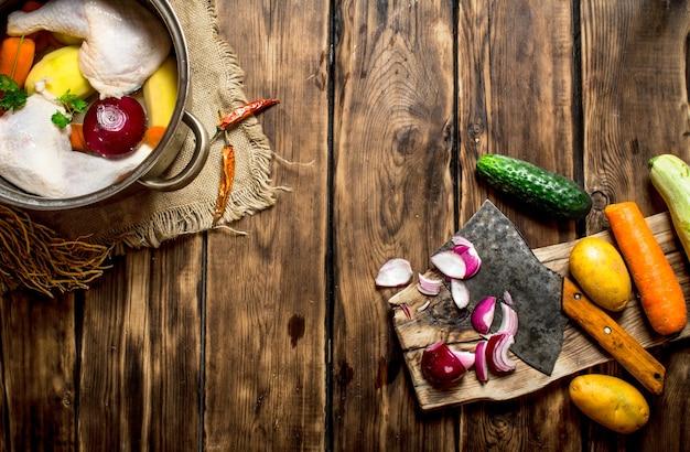 Corte de legumes em caldo de galinha na mesa de madeira.