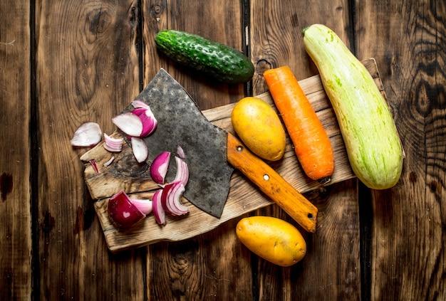 Corte de legumes frescos para a sopa na mesa de madeira.