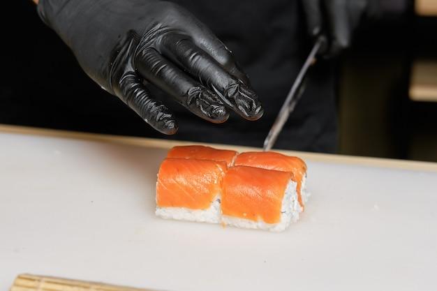 Corte de mão masculino com rolos de salmão de faca