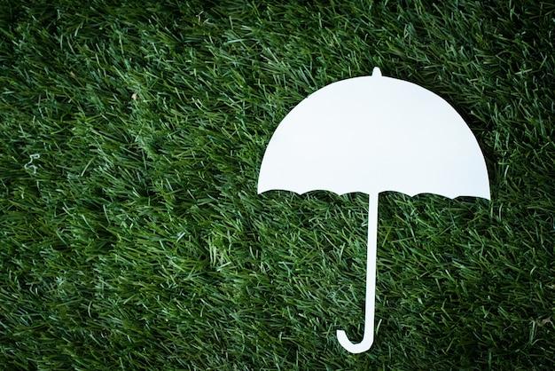 Corte de papel guarda-chuva branco colocar no piso térreo de grama verde