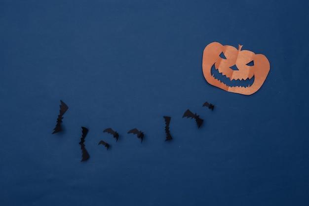 Corte de papel morcegos voadores e abóbora de halloween em fundo azul clássico. fundo de dia das bruxas. vista do topo. postura plana