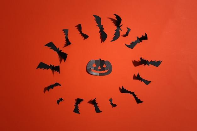 Corte de papel morcegos voadores e abóbora de halloween em fundo laranja brilhante. fundo de dia das bruxas. vista do topo. postura plana