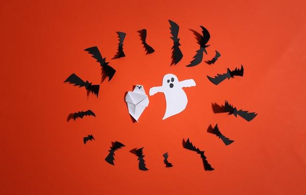 Corte de papel morcegos voadores e fantasmas em fundo laranja brilhante. fundo de dia das bruxas. vista do topo. postura plana