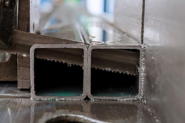 Corte de perfis de aço e tubos em uma serra de fita na produção.