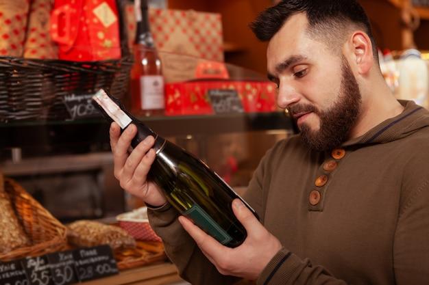 Corte de perto de um homem barbudo examinando uma garrafa de vinho, comprando para a celebração do feriado