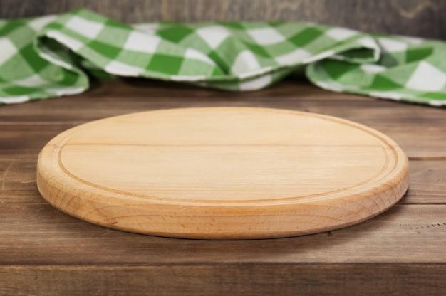 Corte de pizza e tábua de toalha de guardanapo na mesa de madeira rústica, na frente do fundo da prancha