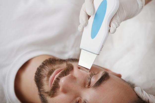 Corte de rosto masculino durante procedimento de ultrassom de limpeza de pele em salão de beleza