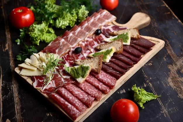 Corte de salsicha e carne com croutons e azeitonas em uma placa de madeira