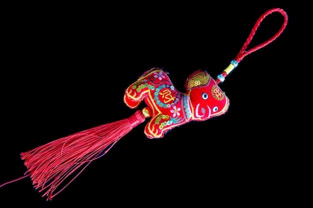 Corte de seda vermelha de amuletos da sorte chineses em fundo preto.