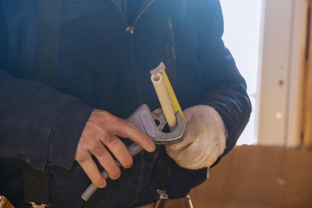 Corte de trabalhador para medir tubo cpvc no canteiro de obras