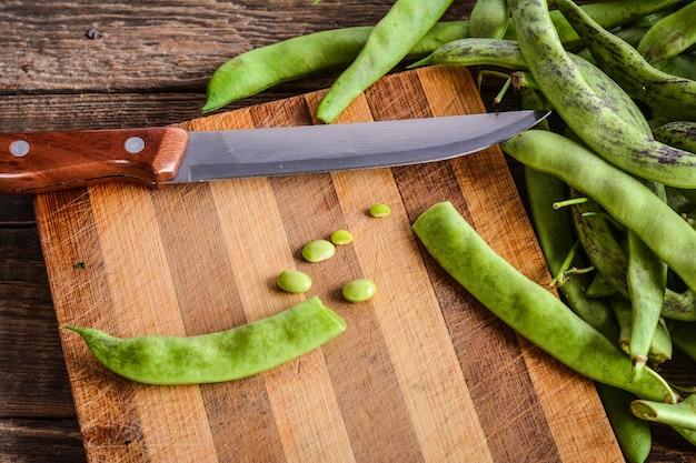 Corte de vagens de feijão verde em uma tábua de cortar