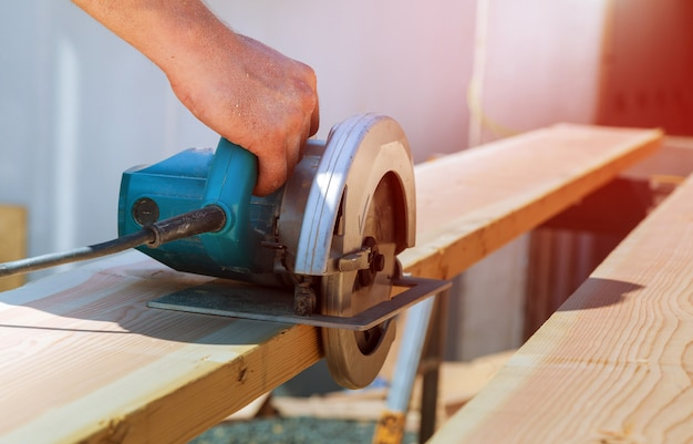Corte de viga de madeira usando uma motosserra elétrica e ferramentas profissionais