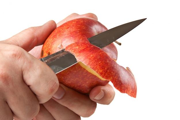 Corte descasque uma maçã com uma faca isolada na superfície branca
