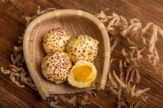 Corte e complete o pão recheado com gema de ovo no vapor na mesa de madeira