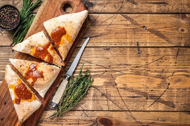 Corte e fatie a pizza calzone fechada com presunto e queijo na tábua de madeira com molho de tomate quente