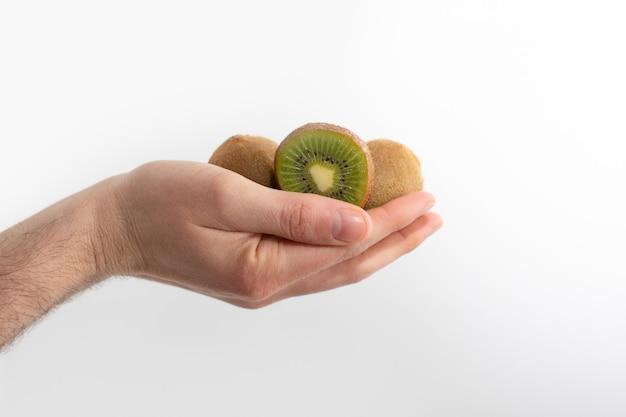 Corte e frutos de kiwi inteiros na mão humana