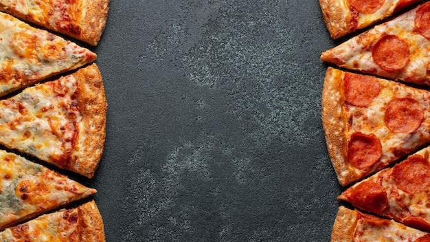 Corte em fatias calabresa deliciosa pizza fresca e pizza quatro queijo em um fundo escuro.