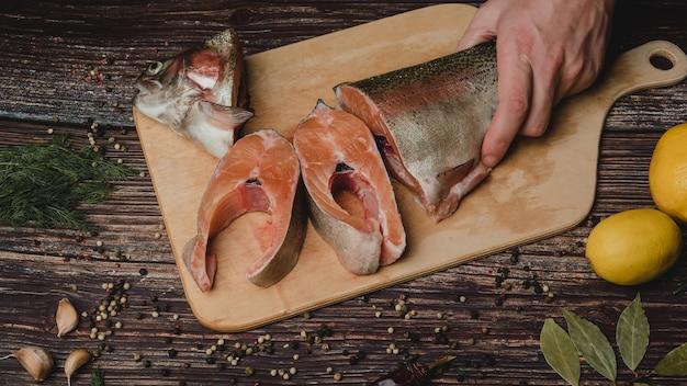 Corte em pedaços truta de peixe vermelho em uma placa de madeira