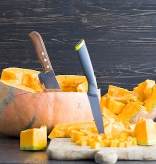 Corte em pedaços uma abóbora laranja madura em outubro, close da comida e estoque para o feriado de halloween, ao lado de facas afiadas Foto Premium