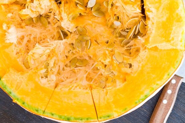 Corte em pedaços uma abóbora laranja madura em outubro, close-up da comida e do estoque para o feriado de halloween, ao lado de facas afiadas Foto Premium