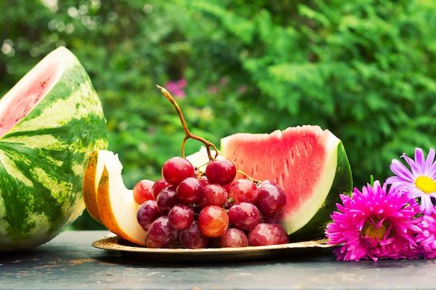 Corte fatias de melão amarelo maduro, melancia, um cacho de uvas e flores ásteres em uma mesa com verde natural. profundidade superficial de campo