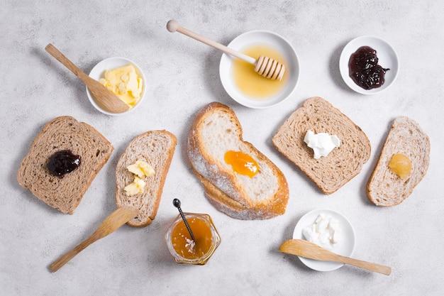 Corte fatias de pão com mel e geléia de café da manhã
