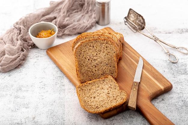 Corte fatias de pão na tábua de madeira com faca alta vista