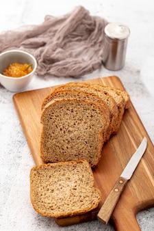 Corte fatias de pão na tábua de madeira com faca