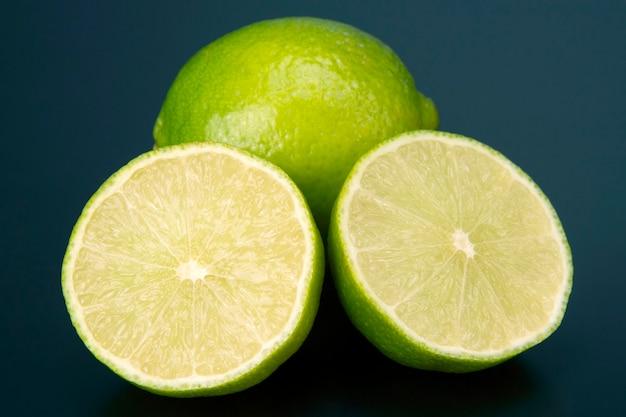 Corte frutas cítricas de limão verde sobre fundo azul. alimentos saudáveis e com vitaminas