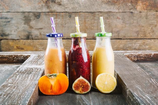 Corte frutas perto de garrafas de smoothie