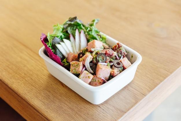 Corte grosso, presunto defumado salada picante com azeitonas pretas na mesa de madeira