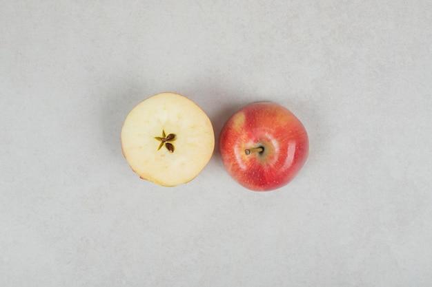 Corte inteiro e meio maçã vermelha na superfície cinza.