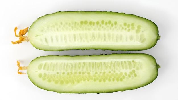 Corte longitudinalmente o pepino no fundo branco. comida natural crua