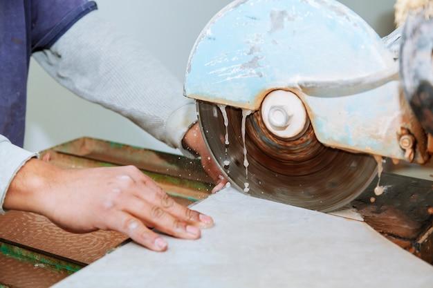 Corte manual de telhas cerâmicas em uma máquina especial para cortar telhas.