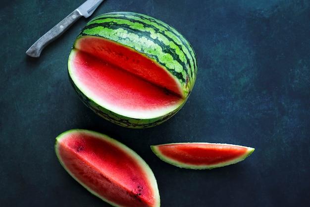Corte melancia e faca na mesa azul