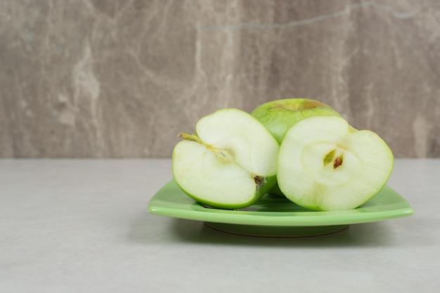 Corte metade das maçãs verdes na placa verde.