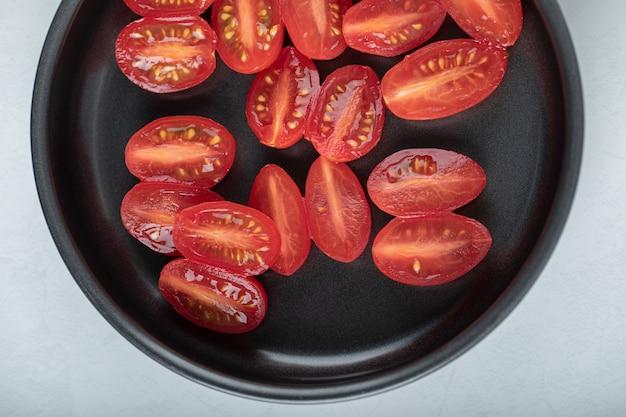 Corte metade dos tomates-cereja vermelhos na frigideira.
