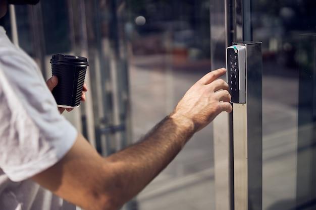 Corte na imagem da mão de um homem ligando o interfone com smartphone ao ar livre.