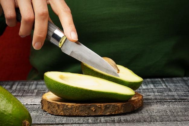 Corte o abacate com uma faca. abacate fresco em uma placa de corte redonda. garota corta um abacate com uma faca. o processo de preparação de alimentos saudáveis