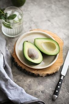 Corte o abacate maduro em um prato sobre uma prancha de madeira ao lado de uma faca e um guardanapo sobre um fundo cinza. alimentos saudáveis, dieta, suplementos alimentares.