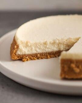 Corte o bolo de cheesecake em um prato branco