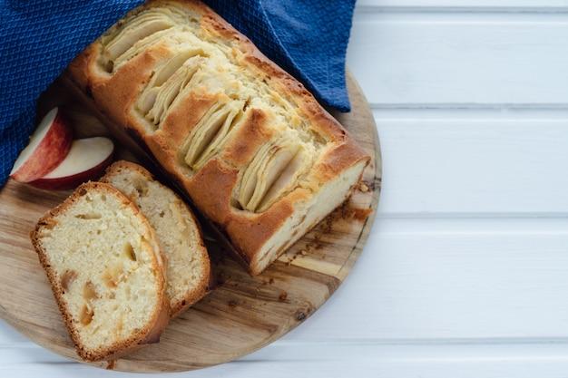 Corte o bolo de maçã em uma mesa branca. copie o espaço. conceito de cozimento.
