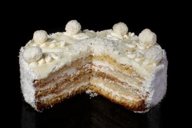 Corte o close-up de um pedaço de bolo branco com raspas de coco em um fundo preto