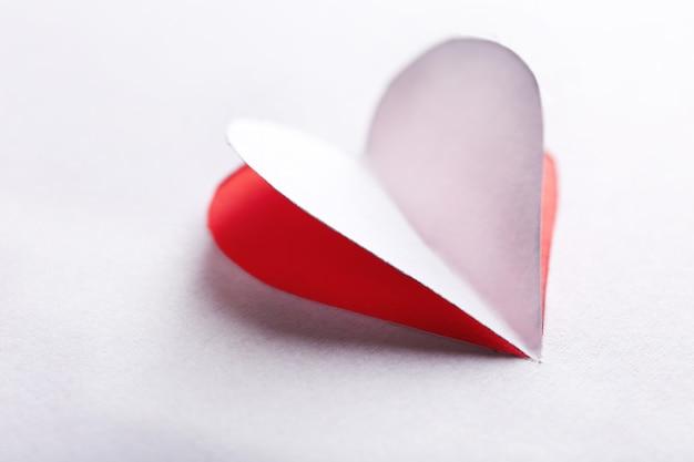 Corte o coração de papel branco em fundo vermelho